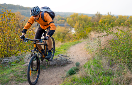 Photo for Cyclist in Orange Riding the Mountain Bike on the Autumn Rocky Trail. Extreme Sport and Enduro Biking Concept. - Royalty Free Image