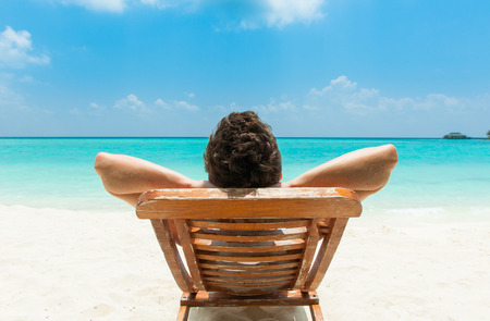 Foto de Man relaxing on beach, ocean view, Maldives island - Imagen libre de derechos