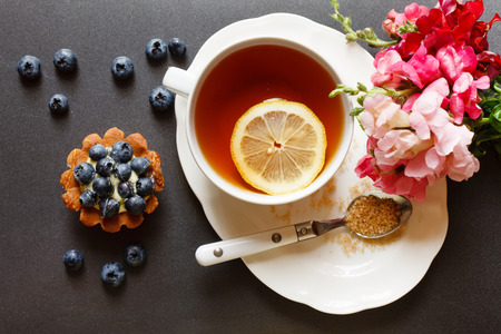 Photo for cup of tea with cake and flowers - Royalty Free Image