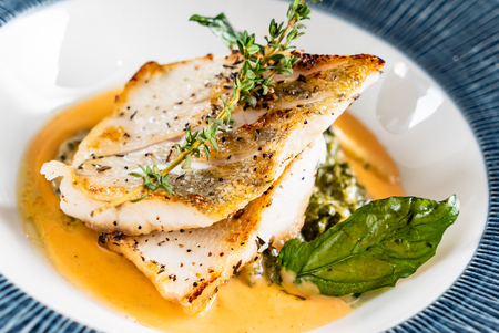 Foto de Fried fish fillet. Cod with sauce and herbs - Imagen libre de derechos