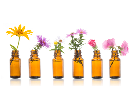 Foto de Natural remedies, bottle -  bach Bottles of essential oil with herbs holy flower. - Imagen libre de derechos