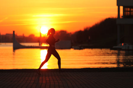 Photo pour Running woman. Runner is jogging on sunrise. Female fitness.  Running Girl In The Beach At Sunset - image libre de droit