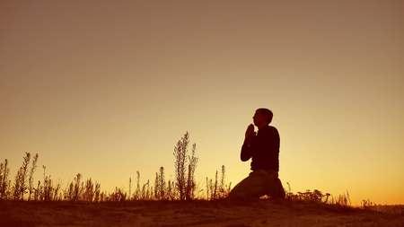 Foto de Silhouette illustration of a man praying outside at beautiful landscape - Imagen libre de derechos