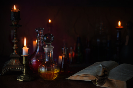 Foto de Magic potion, ancient books and candles on dark background - Imagen libre de derechos