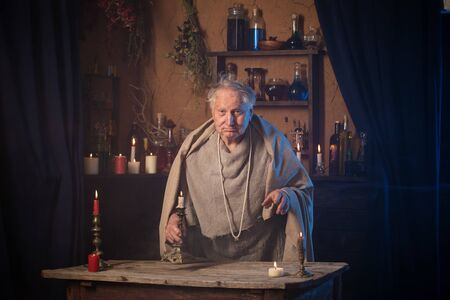 Foto de elderly alchemist monk  with candle - Imagen libre de derechos
