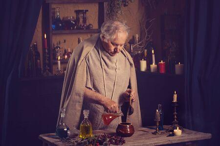Foto de elderly alchemist monk brews  magic potion - Imagen libre de derechos