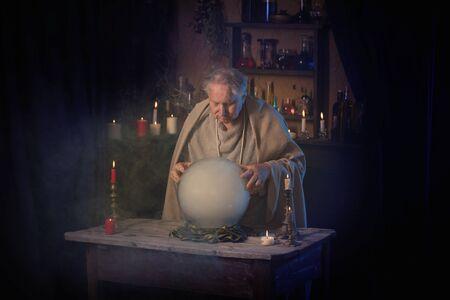 Foto de elderly wizard  with crystal ball - Imagen libre de derechos