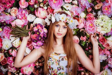 Photo pour A beautiful young girl with flowers bouquet near a floral wall. - image libre de droit