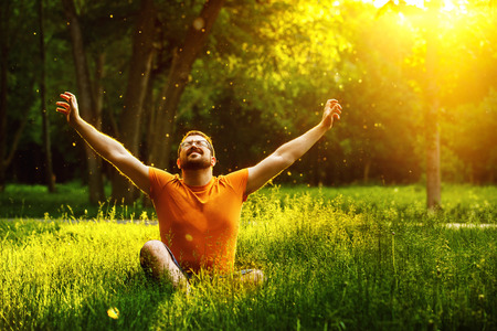 Photo for A happy man is relaxing on green grass with squint eyes and raised up to sky arms at sunny summer day at park background. Concept of wellbeing and healthy lifestyle - Royalty Free Image