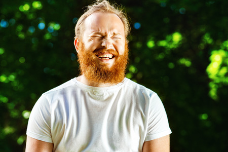 Foto de Closeup portrait of happy mature man with red beard and mustache is laughing at summer green park background. - Imagen libre de derechos