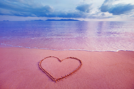 Foto de Closeup image of heart symbol written on sand at pink sea sunrise background. - Imagen libre de derechos