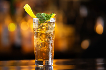 Photo for Closeup glass of long island ice tea cocktail decorated with mint at bar counter background. - Royalty Free Image
