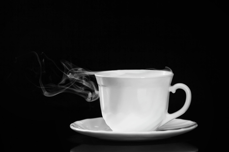 White cup of tea on saucer with smoke isolated at black background.