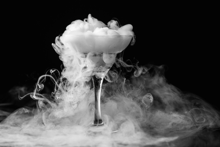 Foto de Closeup glass with white fog at dark background. Chemical reaction of dry ice with water. - Imagen libre de derechos