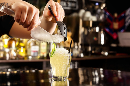 Foto de Bartender is decorating cocktail with crushed ice at bar counter background. - Imagen libre de derechos