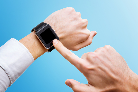 Foto per Businessman is pointing at smart hand with smart watch isolated at blue background. - Immagine Royalty Free