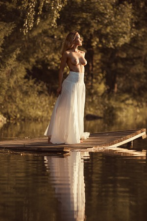 Foto de Sensual young woman with beautiful naked breasts standing nude on wooden platform by the lake at sunset or sunrise - Imagen libre de derechos
