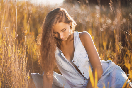 Foto de Beautiful young woman in jean sundress sitting relxed in a field of tall grass on sunset and reading a book - Imagen libre de derechos