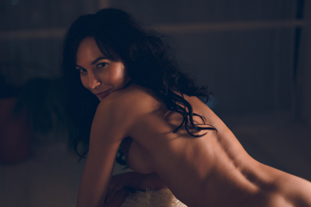 Foto de Playful young woman with awesome muscular back, long black hairs and peach buttocks standing naked or nude in erotic pose in a chair in hotel room and flirting looking in camera - Imagen libre de derechos