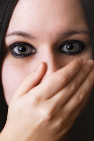 closeup black haired girl covering the face with her hand