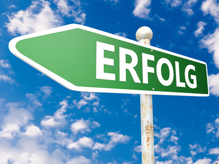 Erfolg - german word for success or achievement - street sign illustration in front of blue sky with clouds.