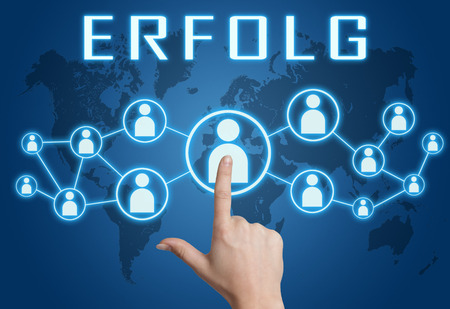Erfolg - german word for success - text concept with hand pressing social icons on blue world map background.