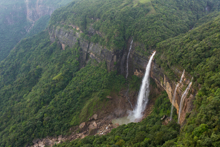 Photo for Nohkalikai waterfall surrounded by high cliffs and woodland and thick vegetation near Cherrapunji, Meghalaya, India. - Royalty Free Image