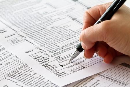 Photo pour tax form with hand and pen  - image libre de droit