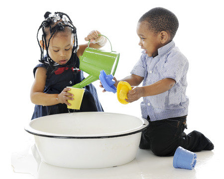 Photo pour A young brother and sister having fun playing in a tub full of water and water toys.  On a white background. - image libre de droit