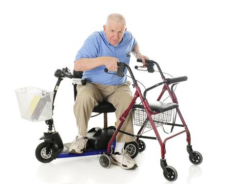 Foto de A senior man transferring from his electric scooter to his wheeling walker.  On a white background. - Imagen libre de derechos