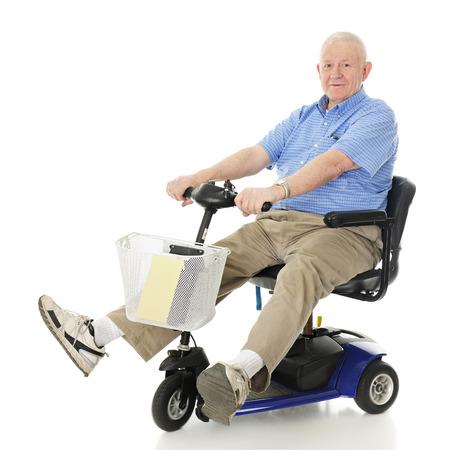 Foto de A senior man delightedly driving his electric scooter.  Motion blur on wheels.  On a white background. - Imagen libre de derechos