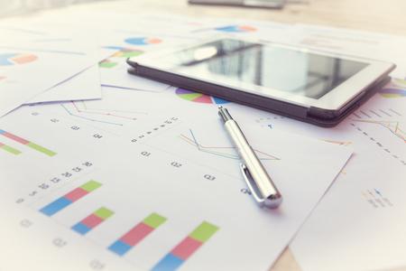 Foto de Modern business workplace with stock market data application , Pen and a digital tablet, on a wood table. - Imagen libre de derechos