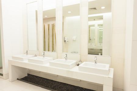 Foto de Commercial bathroom. on white color room. Empty advertisement frames in public toilet - Imagen libre de derechos