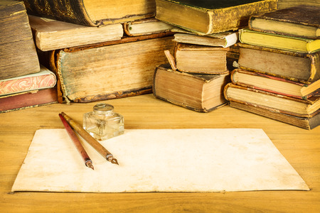 Foto de Sepia toned image of vintage fountain pens with blank paper in front of old books on a table - Imagen libre de derechos