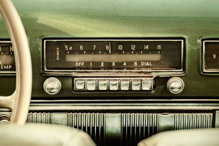 Photo for Retro styled image of an old car radio inside a green classic car - Royalty Free Image