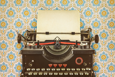 Photo for Retro styled image of an old typewriter with a blank sheet of paper in front of wallpaper with a flower print - Royalty Free Image