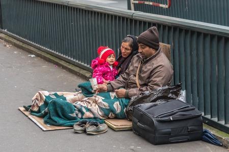 Foto de Homeless family sitting on the street - Imagen libre de derechos