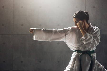 Photo pour Woman in kimono practicing karate - image libre de droit