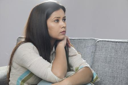 Photo pour Portrait of serious woman sitting on sofa - image libre de droit