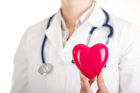 Foto de Female doctors's hand holding red toy heart. Doctor's hand closeup. Medical help prophylaxis or insurance concept. Cardiology carehealth protection and prevention. - Imagen libre de derechos