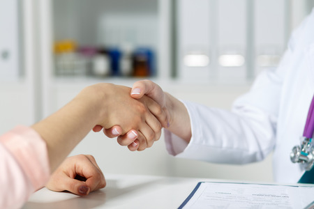 Photo for Female doctor shaking hands with patient. Partnership, trust and medical ethics concept. Handshake with satisfied client. Thankful handclasp for excellent treatment. - Royalty Free Image