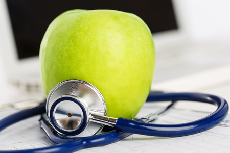 Photo pour Green ripe fresh tasty apple lying on cardiogram chart surrounded with stethoscope. Medical help or insurance concept. Health life and wholesome food concept. Vegetarian lifestyle concept - image libre de droit