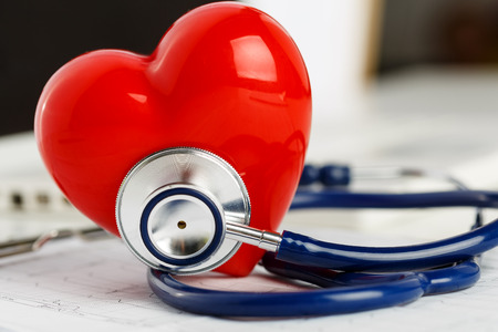 Foto de Medical stethoscope and red toy heart lying on cardiogram chart closeup. Medical help, prophylaxis, disease prevention or insurance concept. Cardiology care,health, protection and prevention - Imagen libre de derechos