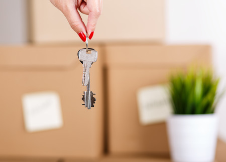 Foto per Female hand holding keys over pile of brown cardboard boxes with house or office goods background. Moving to new place of living concept. - Immagine Royalty Free