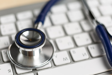 Photo pour Stethoscope head lying on silver keyboard closeup. Medical concept. Modern medicine and high tech equipment concept - image libre de droit