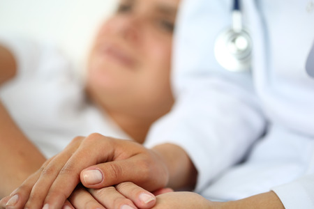 Photo pour Friendly female doctor hands holding patient hand lying in bed for encouragement, empathy, cheering and support while medical examination. Bad news lessening, compassion, trust and ethics concept - image libre de droit