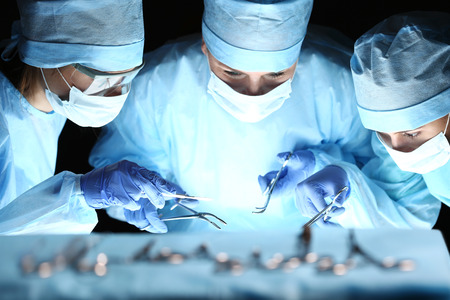 Foto de Group of surgeons at work operating in surgical theatre. Resuscitation medicine team wearing protective masks holding steel medical tools saving patient. Surgery and emergency concept - Imagen libre de derechos