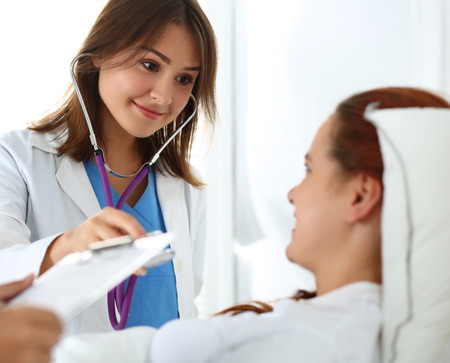 Photo pour Female medicine doctor communicating, examining and listening with stethoscope patient during ward round while nurse filling in patient medical history list. Medical care or insurance concept - image libre de droit