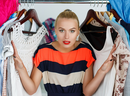 Foto de Beautiful smiling blonde woman standing inside wardrobe rack full of clothes suffering with choice. - Imagen libre de derechos