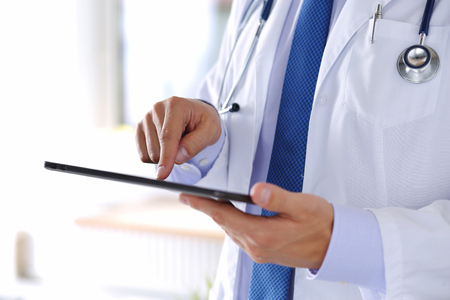 Foto de Male medicine doctor holding digital tablet pc and pointing it with finger.  - Imagen libre de derechos